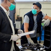 Auto repairman and his manager wearing protective face masks while talking in a workshop.